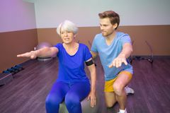 Senior woman exercising assisted by young male trainer. Senior women exercising assisted by a young male trainer Royalty Free Stock Photo