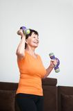 Senior woman exercising with barbells. Smiling happy senior fitness woman excercising with barbells at home Stock Photo