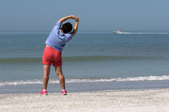 Senior woman exercising on a beach. Royalty Free Stock Image