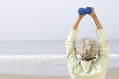 Senior Woman Exercising With Dumbbells On Beach Royalty Free Stock Images