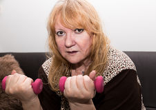 Senior woman exercising with dumbbells. Royalty Free Stock Photos