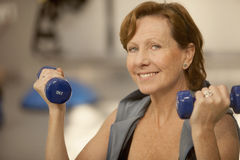 Senior woman exercising with dumbbells Stock Photo