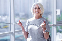 Senior woman exercising with fitness bar. Expressing excitement. Happy elderly lady is standing at sport and doing exercises using fitness bar Stock Photos