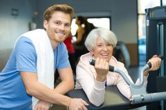 Senior woman exercising with fitness instructor inside gym Stock Photography