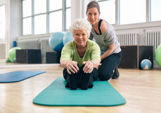 Senior woman exercising at gym with coach Royalty Free Stock Image