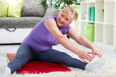 Senior woman exercising in home gym Royalty Free Stock Image