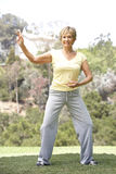 Senior Woman Exercising In Park Stock Photo