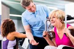 Senior woman exercising with personal Trainer in gym Stock Photos