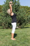 Senior woman is exercising standing outdoors Stock Image