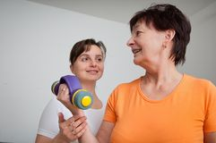 Senior woman exercising with trainer Stock Image