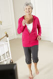 Senior Woman Exercising Whilst Watching Fitness DVD On Television Stock Photos