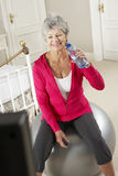 Senior Woman Exercising Whilst Watching Fitness DVD On Television Royalty Free Stock Photography