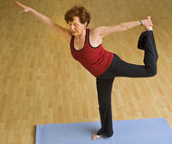 Senior woman exercising yoga. Senior woman doing yoga in a gym Royalty Free Stock Photography