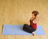 Senior woman exercising yoga. Senior woman doing yoga in a gym Stock Image