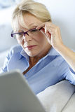 Senior woman with eyeglasses reading news on tablet Stock Image