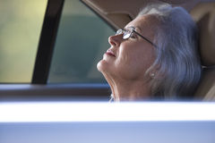 Senior woman with eyes closed in back seat of car Royalty Free Stock Photos