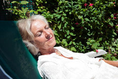 Senior woman with eyes closed relaxing on lounge chair in garden Stock Photography