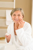 Senior woman with facial cream in bathroom Stock Image