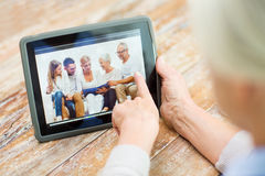Senior woman with family photo on tablet pc screen Royalty Free Stock Images