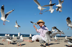 Senior woman feeding flock seagulls at beach. A mature middle-aged woman enjoying the simple pleasures of life and getting back to nature , feeding the birds on Stock Image