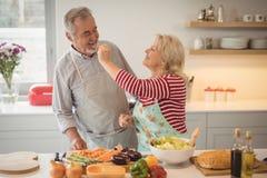 Free Senior Woman Feeding Vegetable Salad To Man In Kitchen Stock Photo - 97362650