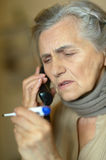 Senior woman feel unwell. Portrait of senior woman with phone and thermometer feel unwell Royalty Free Stock Photos