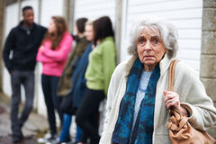 Senior Woman Feeling Intimidated By Group Of Young People. Senior Woman Feels Intimidated By Group Of Young People stock image