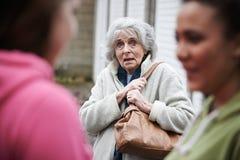 Senior Woman Feeling Intimidated By Teenage Girls. Senior Woman Feels Intimidated By Teenage Girls Royalty Free Stock Photos