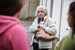 Senior Woman Feeling Intimidated By Teenage Girls Royalty Free Stock Images
