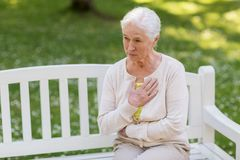 Senior woman feeling sick at summer park. Old age, health problem and people concept - senior woman feeling sick at summer park Stock Photo