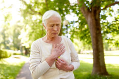 Senior woman feeling sick at summer park. Old age, health problem and people concept - senior woman feeling sick at summer park Royalty Free Stock Photography