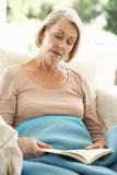 Senior Woman Feeling Unwell Resting Under Blanket Stock Images