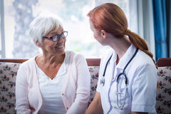 Senior woman and female doctor interacting in living room. Senior women and female doctor interacting in living room at home Stock Photos