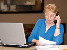 Senior woman filing taxes on line. Getting assistance on the telephone stock photography