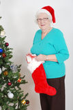 Senior woman filling christmas stocking Stock Photography