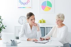 Senior woman filling medical information royalty free stock photography