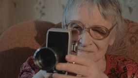 Senior woman filming with retro video camera stock video footage