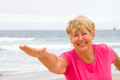 Senior woman fitness. Happy senior woman doing fitness exercise on beach Royalty Free Stock Photography