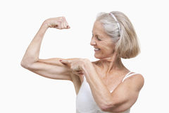 Senior woman flexing muscles against white background Royalty Free Stock Photos