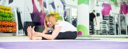 Senior woman stretching in gym, panorama Stock Image