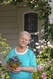 Senior woman with flower in pot in her garden