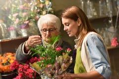 Senior woman in flower shop choosing flowers Royalty Free Stock Images