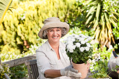 Senior woman with flowers in her garden Royalty Free Stock Photos