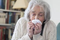 Senior Woman With Flu Blowing Nose At Home