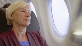 Senior woman flying in airplane. Tired by jet lag female relaxing near window during turbulence. Senior woman flying in airplane in daytime. Tired by jet lag stock video