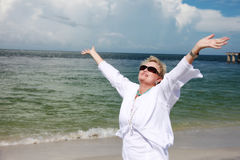 Senior woman freedom/praise. A senior woman on the beach with arms stretched out to sky stock photography