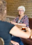 Senior Woman With Friend In Coffeeshop Royalty Free Stock Image
