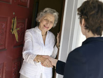 Senior woman friendly greeting. Smiling senior woman with a friendly handshake greets visitor at the front door Stock Photography