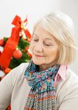Senior Woman In Front Of Christmas Tree. At home Royalty Free Stock Photos
