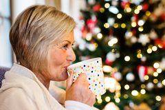 Senior woman in front of Christmas tree. Inside the house, drinking Royalty Free Stock Image